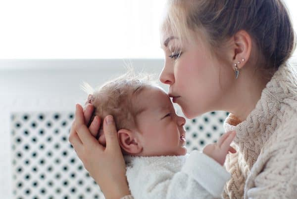 Woman holds her newborn baby and kisses it on forehead