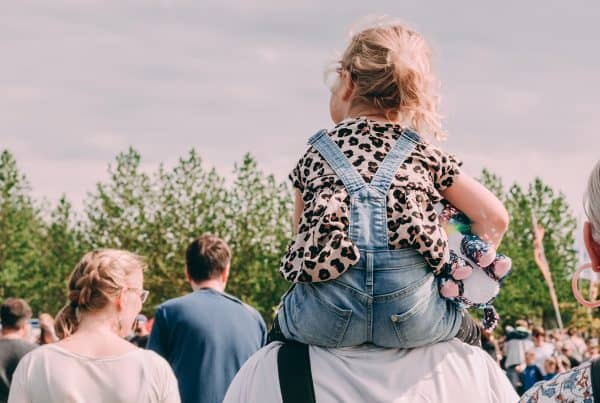 Child rides on grandfather's shoulders at family event